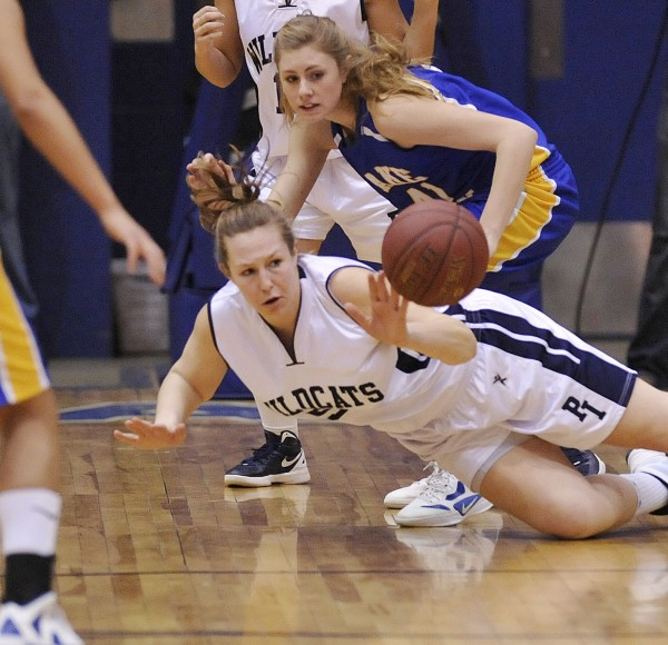 Presque Isle girls basketball player Meredith Stewart (54) comes up with a loose ball from Lake Region player Kelsey Winslow (41) in the first half of their Class B championship game at the Bangor Auditorium on Friday, March 2, 2012.