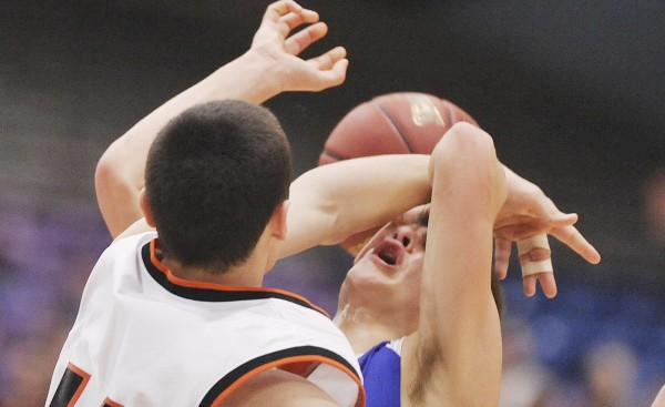 Jonesport-Beals boys basketball player Matthew Alley (right) gets fouled by Forest Hills player Matt Turner in the first half of their Class D championship game in Augusta Saturday, March 3, 2012.