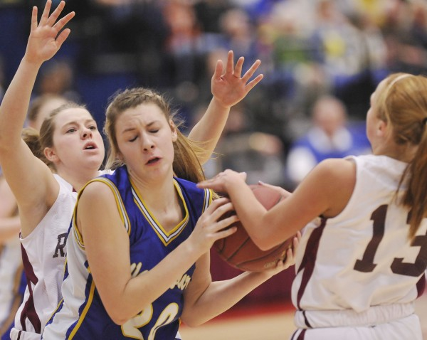 Washburn High School girls basketball player Olivia Doody (20) gets tangled up with Richmond High School girls players Noell Acord (left) and Lindsy Hoopingarner (right) in the first half of their state Class D championship game in Augusta Saturday, March 3, 2012.