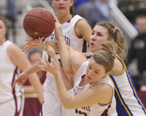 Washburn High School girls basketball player Olivia Doody (center) gets fouled by Richmond player Lindsy Hoopingarner (13) in the first half of their state Class D championship game in Augusta Saturday, March 3, 2012.