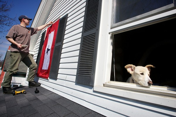 Roger Duncan, a U.S. Navy reservist, hangs a Blue Star flag on his house while his dog Shelby keeps an eye on the street below Monday, March 19, 2012. Duncan will deploy to Afghanistan in April and he doesn't want his wife to have to go on the porch roof and hang it while he's gone.