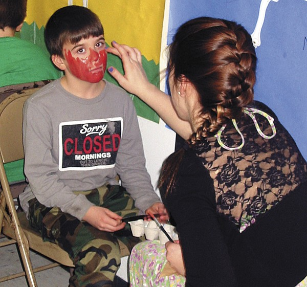 Troy Sands gets his face painted by Bangor High School art student Erika Landon prior to the Fruit Street School Living Art Gallery event.