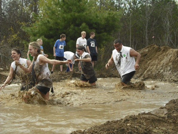 A team of muddy runners slosh their way through a mud pit during the 2011 Into the Mud Challenge in Gorham, sponsored by University of Southern Maine Sport ManagementProgram.