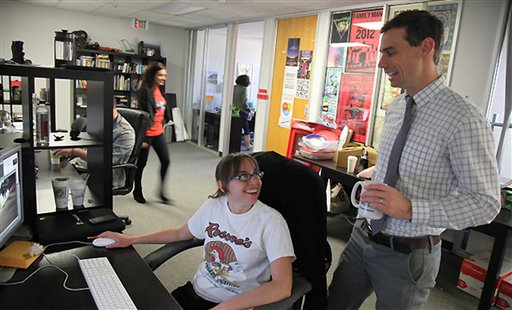 Invisible Children Movement Director Zach Barrows, right, speaks with video editing intern Shannon Lynch about her work on the KONY 2012 project Thursday March 8, 2012 in the groups office in San Diego.