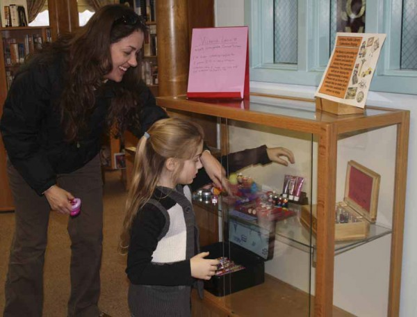 Victoria Leavitt works on placing her collection of 192 lip gloss containers just right in the display case at the Caribou Public Library where they may be viewed over the next two months. Assisting with the display efforts is Victoria's mother Jill.