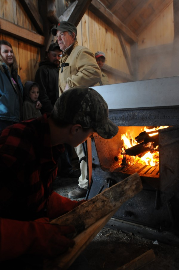 Jason Richard stokes the sap boiler with wood at Simmons and Daughters Maple Syrup in Morrill during Maple Syrup Sunday on Sunday, March 25, 2012.
