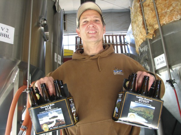 Doug Maffucci, owner of Atlantic Brewing Co. in Bar Harbor, displays two brands of beer that his company bought with its acquisition of crosstown rival Bar Harbor Brewing Co. in 2009.