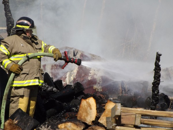 A firefighter with the Newport Fire Department attempts to put out some remaining flames at a fire that consumed three storage trailers on Rutland Road in Newport on Thursday, March 22, 2012. No one was hurt.