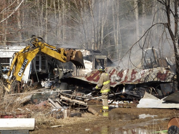 A backhoe is used to remove debris while a firefighter with the Newport Fire Department looks on during a fire the destroyed three storage trailers on the Rutland Road in Newport on Thursday, March 22, 2012. No one was hurt.