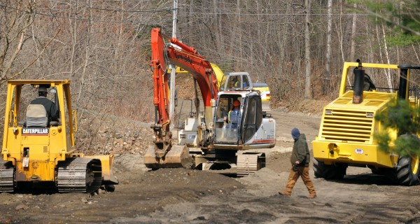 Construction crews work on repairing the Swetts Pond Road in Orrington on Monday, March 27, 2012. The roadway and several driveways were washed away when a beaver dam burst Friday evening.