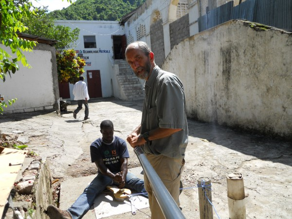 Konbit Sante staffer Josue Limprevil (seated) and Executive Director Nate Nickerson work together to install the Bison deep-well pump in Well #3 at the Justinian Hospital. The well and pump will supplement the water needs for the Justinian, a 250 bed public hospital located in Cap-Haitien, Haiti.
