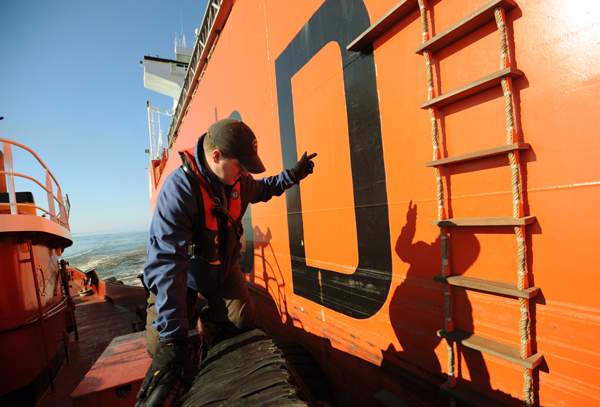 Pilot Adam Philbrook uses hand signals on Wednesday, March 21, 2012  to help guide the tug he is riding closer to the pilot's ladder aboard the Bow Saga tanker carrying caustic soda headed for Mack Point. Philbrook is an apprentice pilot and was brought aboard the large tanker to allow him the added experience of the larger ship. Philbrook was sucessfully in guiding the tanker to its berth at Mack Point in Searsport.