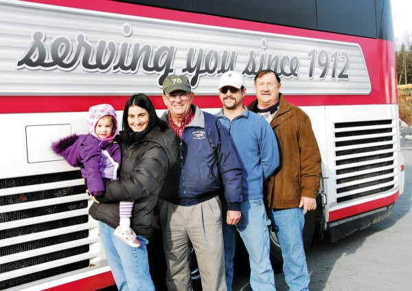 "Four generations of Cyrs stand beside a new motorcoach emblazoned with ""serving you since 1912."" Representing the family are (from left) Ruby Whitmore; her mother, Becky Whitmore (Joe Cyr's daughter), bookkeeper; Joe Cyr, president; Mike Cyr (Joe's son), charter manager; and Pete Cyr (Joe's brother), body man."