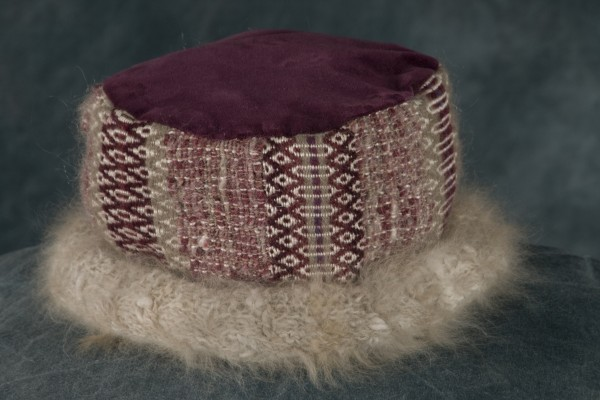 The 2012 Mahitabelle Collection hat is created by Rose Whitehead of Waldo, who uses the brushed out hair of her Angora rabbit, Mihitabelle, for this special line. The hat has a velvet top and lining. The woven portions are made with bands of traditional Scandinavian rosengang pattern separated by handspun yarns, and the wool brim is covered in woven Angora fur from Mihitabelle.