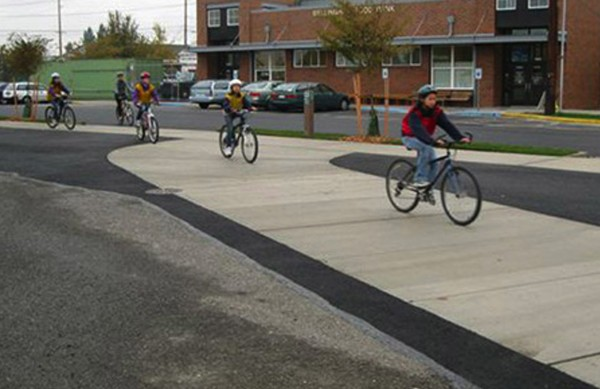 Children in in Bellingham, Wash., ride their bikes over the sidewalk  made with an aggregate of concrete and 400 crushed toilets.