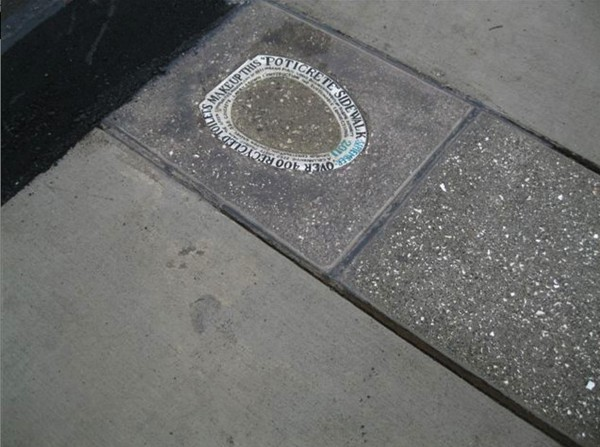 An inscribed toilet seat is embedded into a Bellingham, Wash., sidewalk, making note of the 400 toilets that were crushed and mixed into a new poticrete sidewalk there.