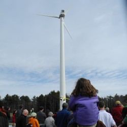 Elana Allen, 5, of Appleton sat on her dad, David's shoulders, and held a plastic twirlygig at the ribbon-cutting ceremony for a new wind turbine at Camden Hills Regional High School in Rockport. She likely will graduate with the class of 2025.