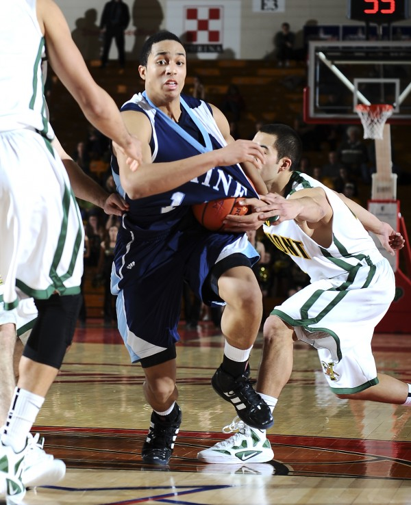 Maine's Justin Edwards drives the lane despite Vermont's Four McGlynn's best efforts to defend the play during an America East quarterfinal Saturday night in West Hartford, Conn. Vermont held off the Black Bears 50-40.