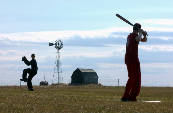 Justin Bouchard (left) winds up a pitch for Jordan Haines as they hone their baseball skills in a field between the two boys' homes in Caribou on a sunny afternoon in 2003.
