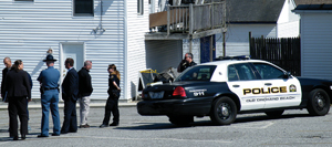 Detectives from the Maine State Police Major Crimes Unit and Old Orchard Beach Police confer Saturday afternoon near 29 Old Orchard St. State Police said the body of Roger White was found behind the fence in the right of the photo about 9 a.m. Saturday by a neighbor.