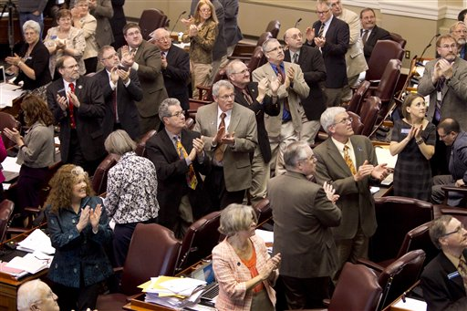 In this April 13, 2012 photo, legislators on the Republican side of the aisle stand and applaud visitors in the House Chamber during a session, at the State House in Augusta, Maine. From cutbacks in MaineCare to slashed income taxes, Gov. Paul LePage and Maine's Republican-majority Legislature have left their mark on the 2012 election-year session.