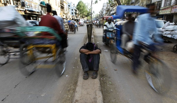A daily wage worker catches a nap while sitting on a narrow road divider at a wholesale market in New Delhi, India on Tuesday, April 17, 2012. India's headline inflation rose 6.9 percent in March, faster than expected because of rising food prices, government data showed Monday.