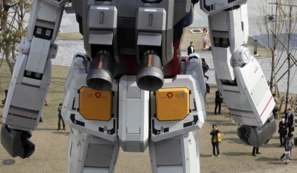 People on the ground are dwarfed by a full-size model of Japan's popular robot animation character Gundam standing in front of a new shopping mall in Tokyo's Odaiba waterfront area on Tuesday, April 17, 2012. The 60-foot-tall Gundam greets shoppers at Diver City Tokyo Plaza which opens on Thursday.