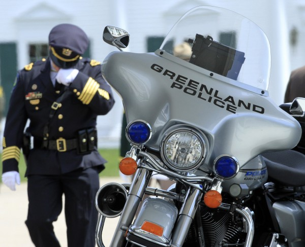 An officer walks by the motorcycle of Greenland Police chief Michael Maloney, Wednesday April 18, 2012 in Hampton, N.H. during a wake service for the chief, who died when he and other officers were trying to serve a warrant at a Greenland home. Four other officers were injured.
