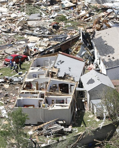 People examine the damage in the Oaklawn neighborhood in Wichita, Kan., on Sunday, April 15, 2012, caused by one of several tornadoes that hit the state on Saturday.