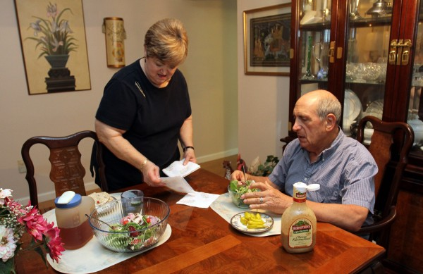 The people you are closest to can have the worst effects on your diet. Here, Madeline Schwartz puts out napkins as she and her husband, Ed, eat lunch in Weston, Fla.