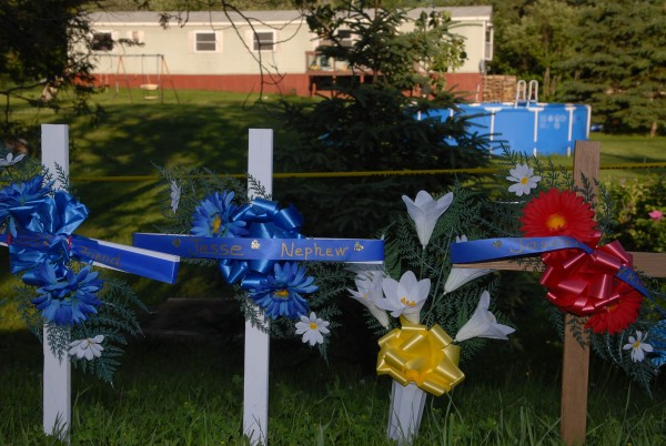 Three memorial crosses as well as flower arrangements were placed along Route 1 in Amity in front of the mobile home where Jesse Ryan, 10, his father, Jeffrey Ryan, 55, and Jason Dehahn, 30, were found dead in June 2010.