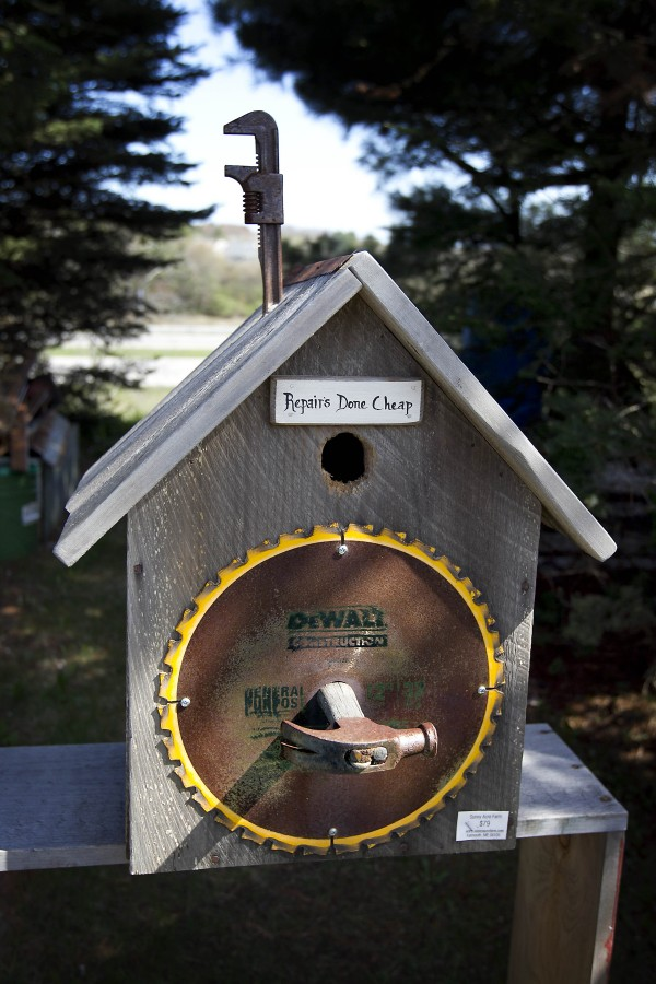 A wrench, hammer and circular saw blades accessorize a birdhouse built by Tony DiPietro.