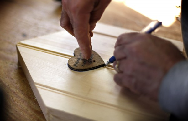 Tony DiPietro traces a heart shape that will be cut out on the front of a birdhouse.