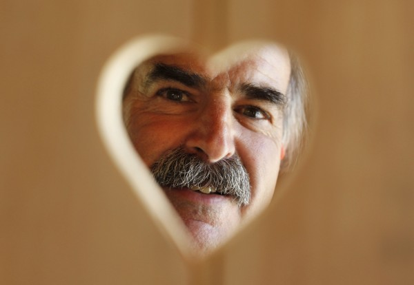 Tony DiPietro examines a heart-shaped hole cut in a board that will part of a birdhouse.