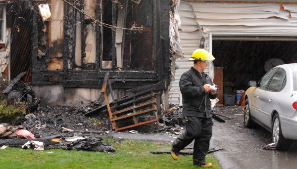 Edward Archer, senior investigator with the state fire marshal's office, takes pictures of a home in Brewer that caught on fire early Monday morning.