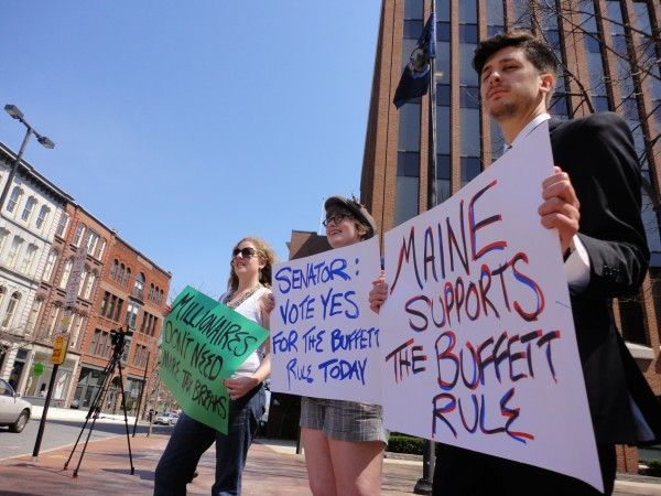 Delia Gorham (from left), Kaiulani Anderson-Andrei and Wells Lyons hold up signs near Canal Plaza in Portland around midday Monday, April 16, 2012, representing the Maine League of Young Voters. The league held the demonstration to raise awareness of the &quotBuffett Rule,&quot in which millionaires in America would be taxed a consistent 30 percent on income.