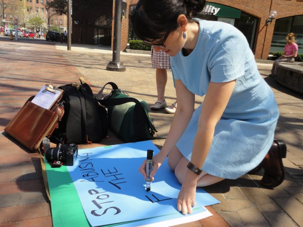 Sarah Schindler, a volunteer with the Maine League of Young Voters, makes a sign Monday, April 16, 2012, during a league demonstration in Portland in support of the Buffett Rule.
