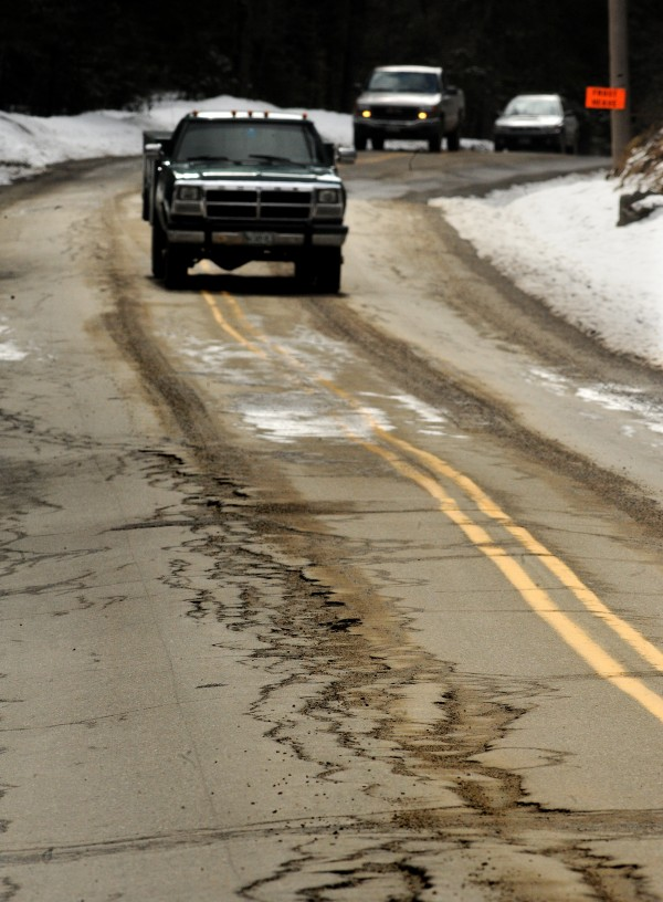 Motorists drive on Route 46 in Dedham in March 2011. Sections of this road are notoriously rough during the spring, forcing drivers to slow to a crawl to negotiate frost heaves and potholes.