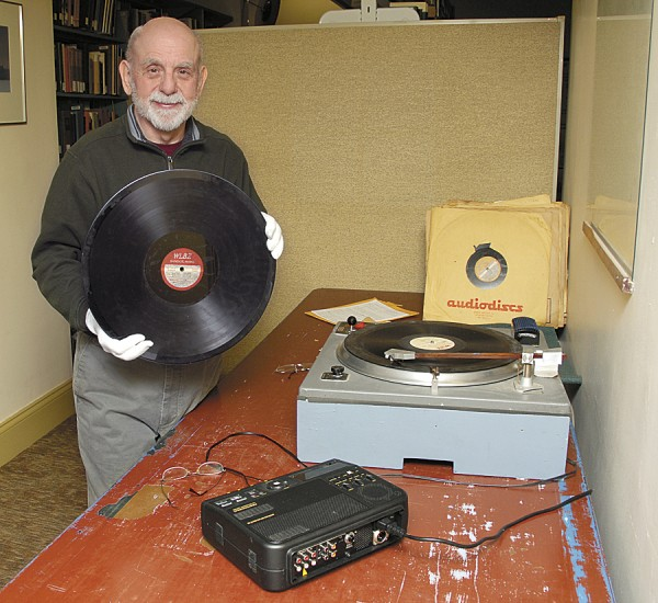 """Barry Darling displays a WLBZ radio electrical transcription — which looks like a large record — that contains live radio programs from the 1940s. He has been """"transcribing"""" some 200 """"ETs,"""" as they are known, by playing each on the turntable set on the table beside him. The turntable transmits the recorded data to a device (foreground) that transfers the signal to a CD."""