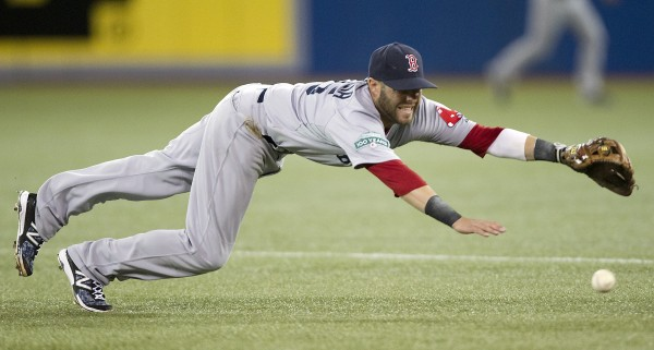 Boston Red Sox second baseman Dustin Pedroia dives to try to stop a single by Toronto Blue Jays' Kelly Johnson in the third inning  in Toronto on Tuesday, April 10, 2012.
