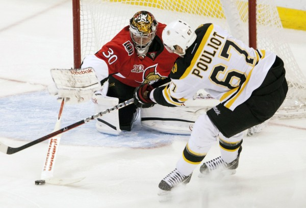 Ottawa Senators goalie and former University of Maine standout Ben Bishop, left, poke-checks the puck away from Boston Bruins left wing Benoit Pouliot in front of the net during first-period NHL hockey game action in Ottawa, Ontario, Thursday, April 5, 2012.