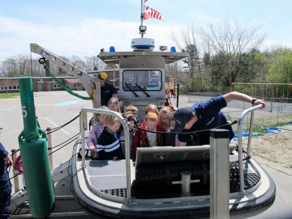 U.S. Coast Guardsman DC Joshua Schmidt demonstrates some of the features of a 26-foot buoy tending boat to students at Jewett Elementary School in Bucksport on Wednesday, April 25, 2012. Members of the Coast Guard's Southwest Harbor station visited the school as part of a boating safety program.