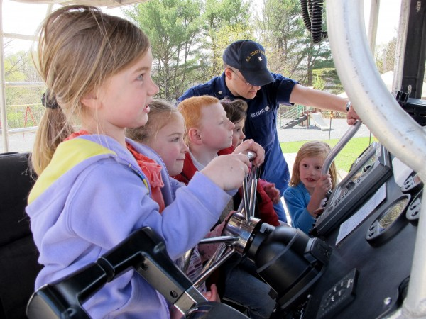 Jewett Elementary School kindergartners (from left) Elizabeth Rainey, Maureen Tyne, Tristan Davis and Guinevere Berry get to sit behind the controls of a 26-foot U.S. Coast Guard boat on Wednesday, April 25, 2012, as part of a boating safety demonstration at the school.