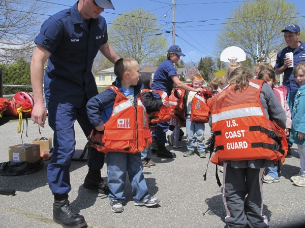 Crew members from the U.S. Coast Guard's Southwest Harbor station help kindergartners from Jewett Elementary School in Bucksport zip into oversized lifejackets on Wednesday, April 25, 2012. Although much too big for real-life use on the water, the jackets were a big hit with the children and allowed the Coast Guard crew to talk about the importance of wearing life preservers.