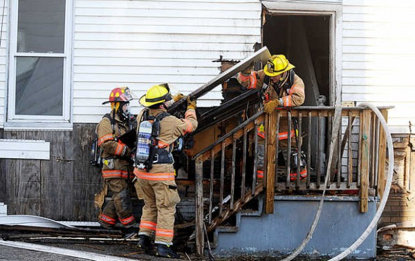 Lewiston firefighters remove a door at 158 Pierce St. in Lewiston on Saturday, March 31, 2012 as they work to extinguish a fire in the building.