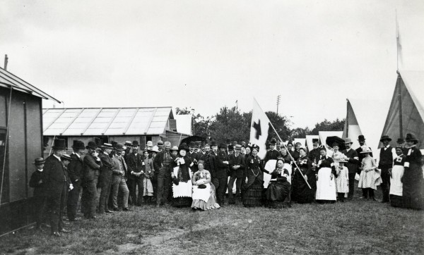 A May 1887 National Guard camp in Washington. Clara Barton, seen standing in front of the American Red Cross flag, was invited to direct the camp's hospital.