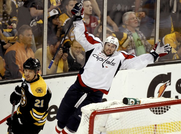 Troy Brouwer of the Washington Capitals celebrates his winning goal as Boston Bruins defenseman Andrew Ference (21) skates away during the third period of Washington's 4-3 win in Game 5 in a first-round playoff hockey series in Boston on Saturday, April 21, 2012.