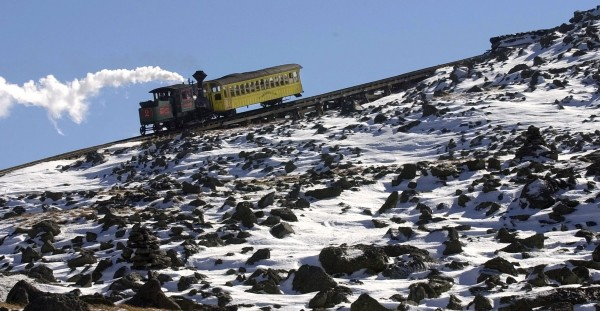 This Oct. 8, 2003, file photo shows the Cog Railway make its way to the top of the snow covered Mount Washington, N.H.  New Hampshire's Mount Washington Cog Railway, the world's first mountain climbing train, opens its 143rd season Saturday, April 28, 2012, chugging tourists, nature lovers and thrill seekers up the highest peak in the Northeast United States.