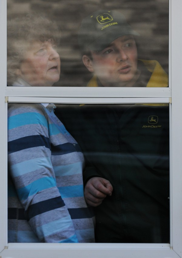 Cindy Burke and her son Casey wait by the family's kitchen door on Tuesday, April 3, 2012, looking for Casey's ride to an outing in town to celebrate with other men with disabilities.