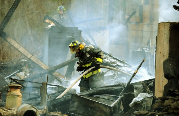 A Newburgh firefighter pulls a hose out of the remains of a house on Merchant Road in Hampden on Sunday, April 15, 2012. Numerous fire departments incuding Bangor went to the fire which was located off a dirt road in Hampden.